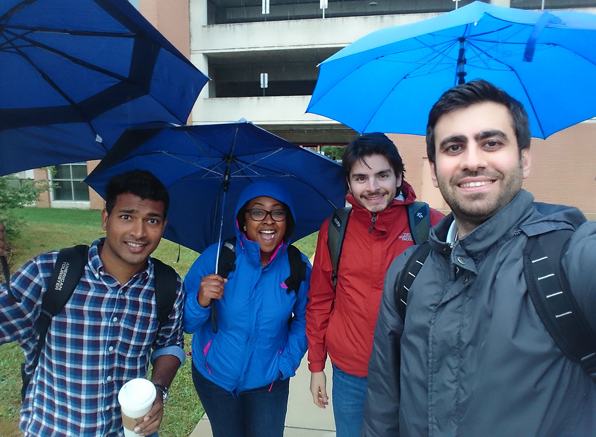 Graduate students in the PhD in PHSR program pose for group photo in the rain.