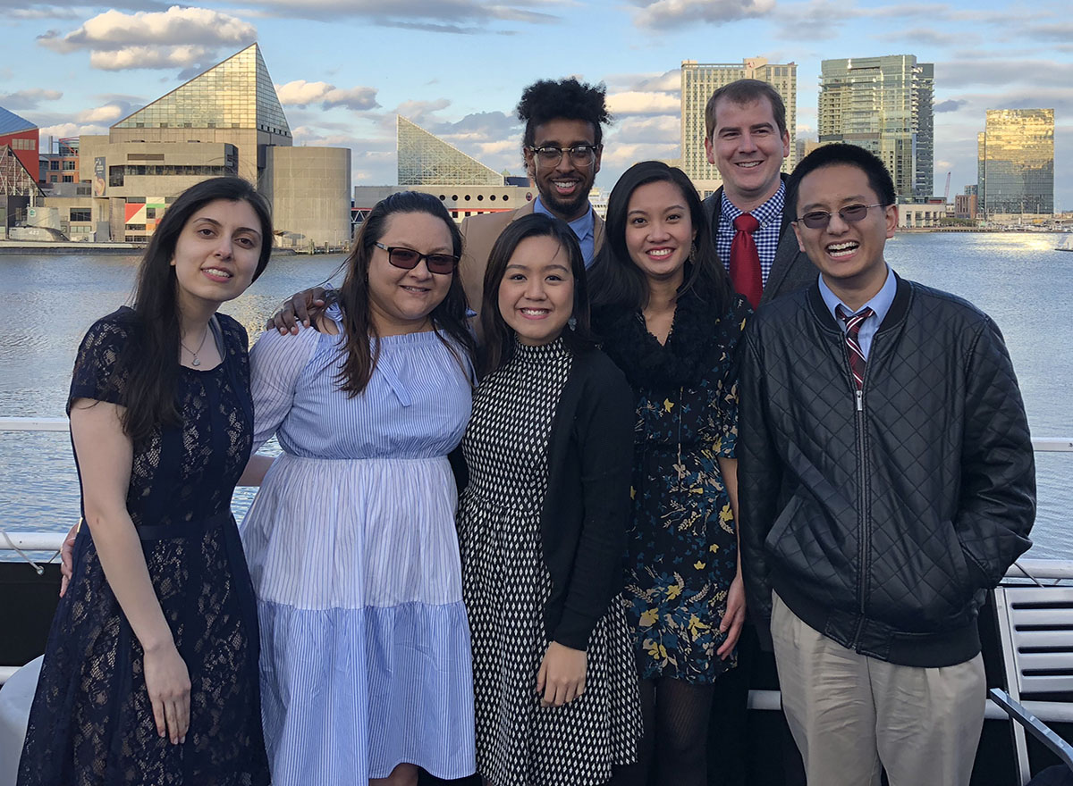 Student pharmacists pose for group photo in front of Baltimore skyline.