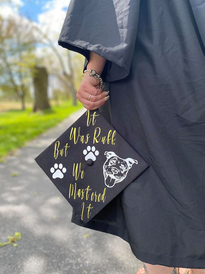 """Graduate student displays graduation cap with message, """"It was ruff, but we mastered it."""""""